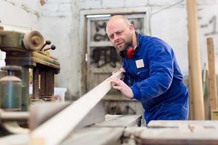manufactory: Professional worker at a wood processing manufactory is cutting planks of wood on a lathe Stock Photo