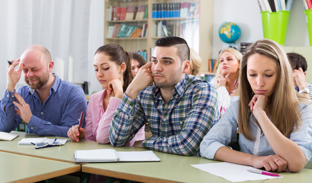 deadpan: Portrait of bored adult students sitting at lesson in classroom