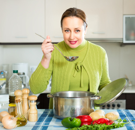 ordinary woman: Ordinary  woman with ladle testing soup from pan in domestic kitchen