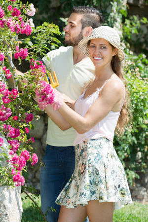 horticultural: Young couple in flowers garden with horticultural sundry at summer day