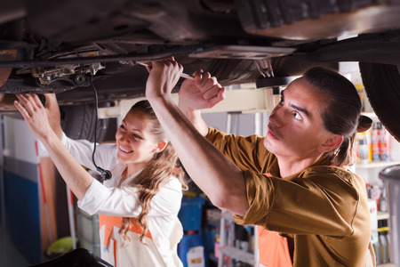 two car garage: Portrait of two troubleshooters repairing car at garage