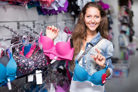 brassiere: Young attractive woman buying brassiere at clothing store