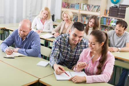 adult student: Attentive adult students industriously writing down summary at a classroom Stock Photo