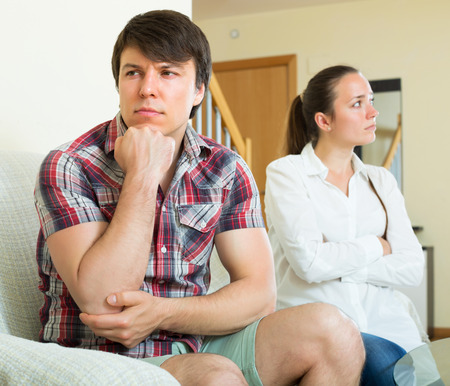 squabble: Unhappy guy and sad woman during conflict in living room