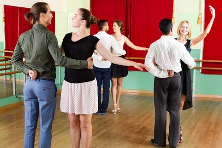 merry dancers: Tree smiling beautiful  couples dancing waltz in dancing-class