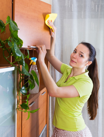 25s: Young brunette girl dusting wooden furiture with rag and cleanser at home