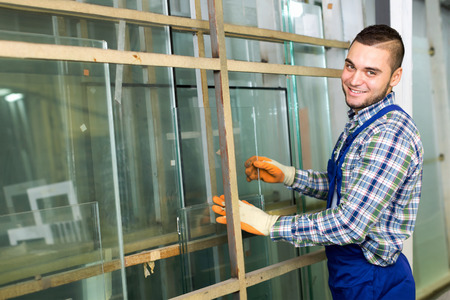 glasswear: Worker in coverall measuring glass at factory Stock Photo