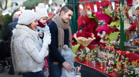niños de compras: Happy sonrientes padres con niñas en mostrador con Flor de Pascua. Foco bajo