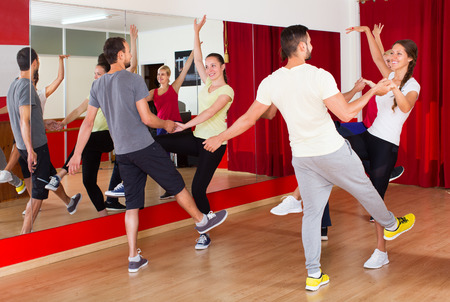 unprofessional: Happy men and women enjoying the active dance in the dance studio Stock Photo
