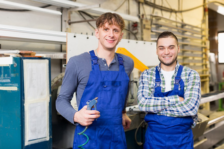 toolroom: Two positive employes do his job on a machine in factory