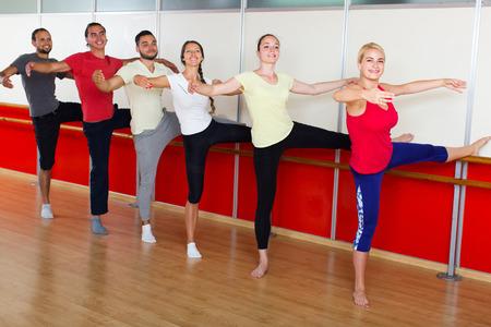 Grupo de hombres españoles felices y mujeres que practican en la barra de ballet Foto de archivo