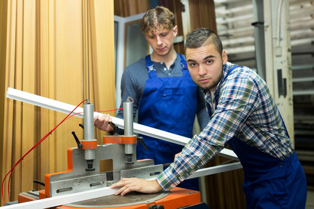 toolroom: Positive men working together on a machine in factory