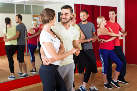 danza clasica: Grupo de personas ruso sonrientes que bailan salsa en el estudio Foto de archivo