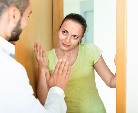 strife: Irritated young couple  quarreling at the door Stock Photo