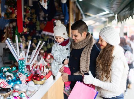 niños de compras: Padres con pequeña hija sonrientes en el mostrador del mercado de Navidad Foto de archivo