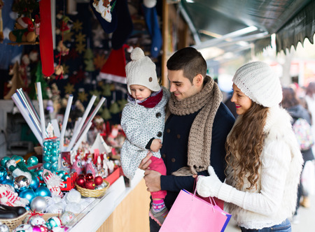 holidays: Smiling parents with small daughter at counter of X-mas market Stock Photo