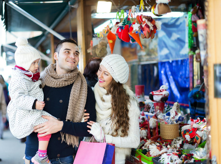public market: Happy family choosing Christmas decoration at Christmas market. All family on focus
