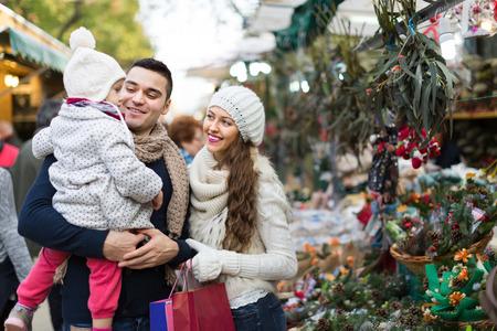 flor de pascua: Happy sonrientes padres con pequeña hija en el mostrador con Poinsettia. Foco bajo Foto de archivo
