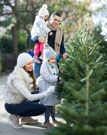Familia feliz de cuatro elegir el árbol de Navidad en el mercado. Foco bajo