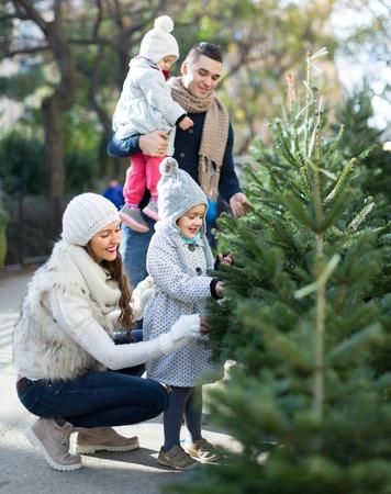 Glückliche Familie von vier Wahl Weihnachtsbaum am Markt. Flachen Fokus
