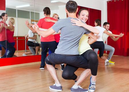 baile latino: Hombres sonrientes felices y mujeres bailando bachata juntos en el estudio de danza