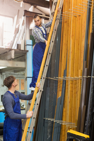 toolroom: Production workmen in uniform with different PVC window profiles Stock Photo
