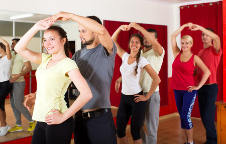 Smiling young people dancing Latino dance in class