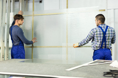 enginery: Two careful young workers cutting glass for windows at workshop
