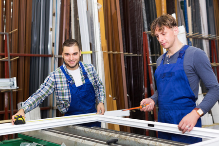 workmen: Two careful workmen inspecting windows with shutter at workshop indoor Stock Photo