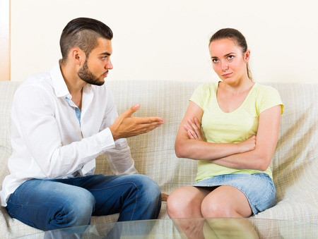 strife: Unhappy couple sitting at the sofa and having quarrel. Focus on girl Stock Photo