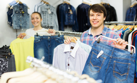 choosing clothes: Happy couple choosing clothes at clothing shop