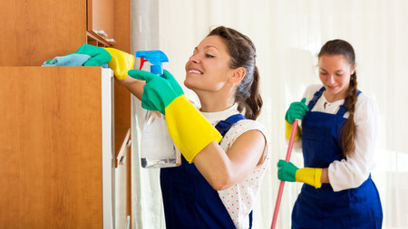 company employee: Cheerful young female workers cleaning company ready to start work Stock Photo