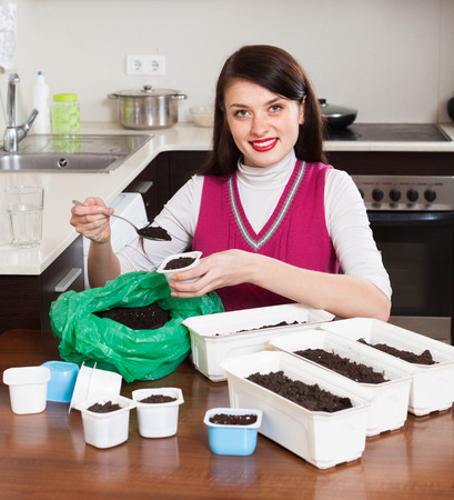 Girl making  ground for sprouts at table in home kitchen Stock Photo