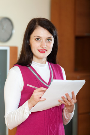 home office interior: Smiling brunette woman filling in  documents at home or office interior Stock Photo