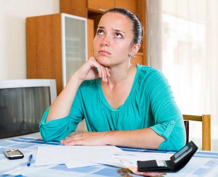 tired face: Sad american thoughtful girl sits with her bills on the table