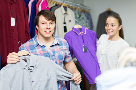happy customer: Positive couple choosing clothes in the mall