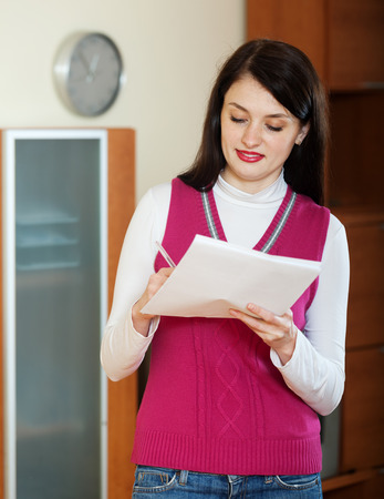filling in: brunette woman filling in paper at home or office interior Stock Photo
