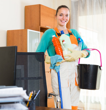 household tasks: happy professional young american cleaner  cleaning the office