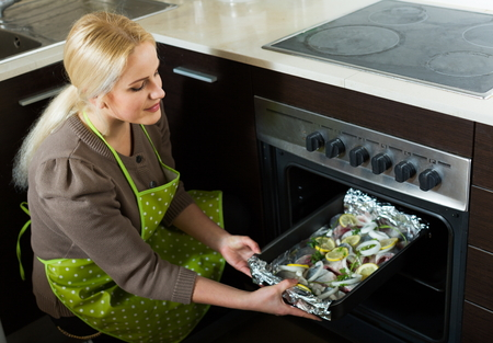fryingpan: Young woman cooking fish  in oven at home kitchen Stock Photo