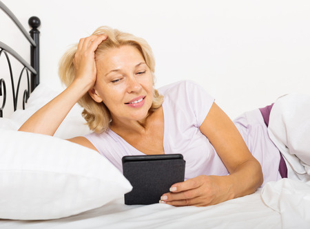electronic book: mature woman with electronic book laying in  bed at home