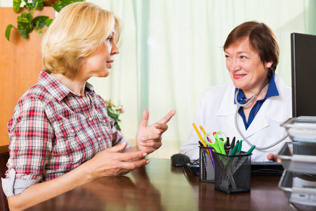 health professionals: Smiling mature female doctor consulting patient Stock Photo