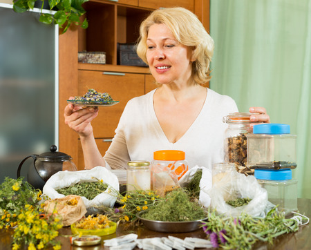 heterogeneous: Smiling mature woman sitting at table with aroma herbs in home