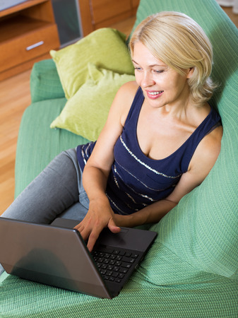 netbook: mature woman working with netbook and sitting on sofa in living room