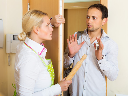 threatens: Angry girl threatens with rolling-pin for a frightened young man