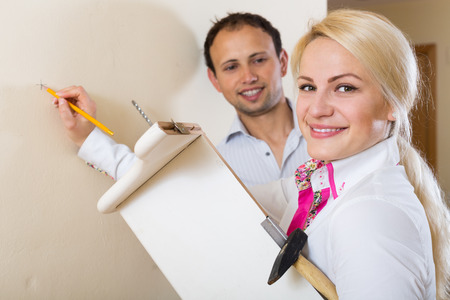 modifying: Russian couple hangs bookshelf on a wall Stock Photo