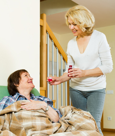 linctus: Mature woman visiting  sick elderly friend and giving her a linctus at home