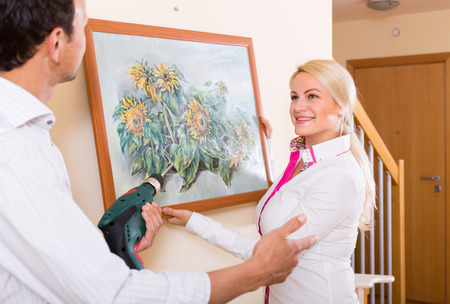 modifying: Young man and blonde smiling woman hanging art picture in frame. Focus on woman