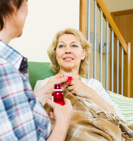 linctus: woman visiting  sick friend and giving her a linctus at home Stock Photo