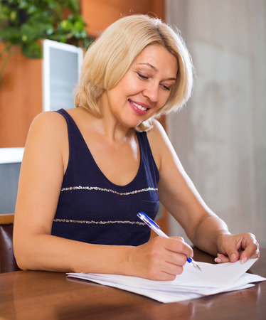 parsimony: Portrait of mature smiling woman with financial documents at home Stock Photo