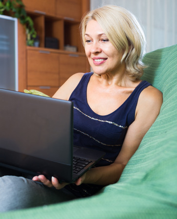 netbook: mature woman 50-60 years old with netbook sitting on sofa in living room